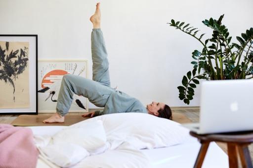 Angela Sauer in der Pilates Übung Bridging, im Vordergrund die Rückseite des Laptops und Bett