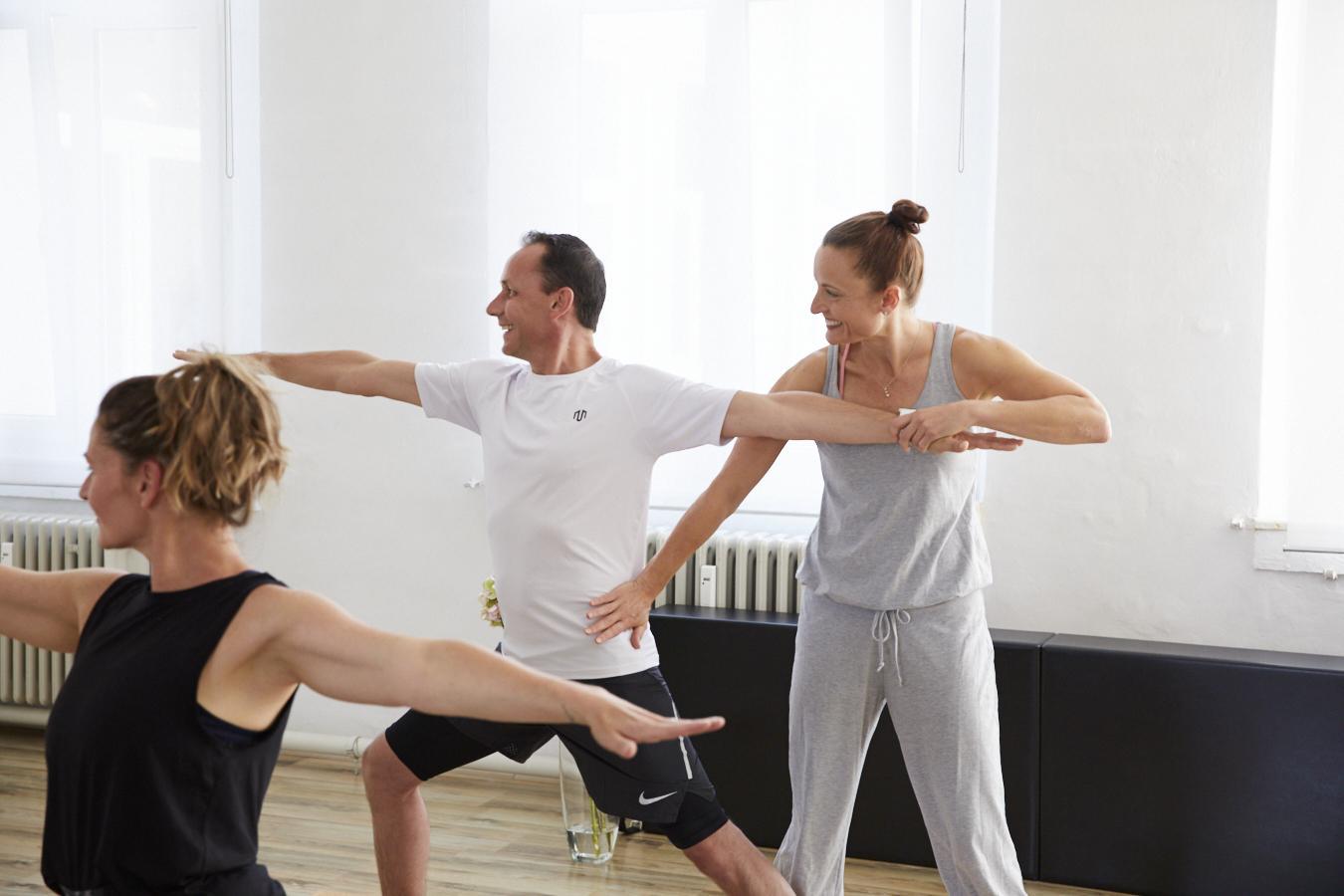Kristina beim Unterrichten von einer Yogahaltung, während sie einen Teilnehmer korrigiert im Pilates & Yoga Studio 1 in Pforzheim
